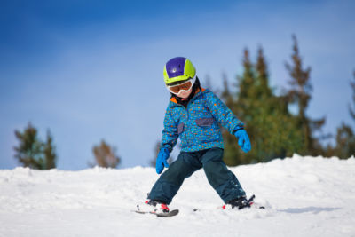 Small boy in ski mask and helmet learns skiing down the hill with legs sliding in different directions